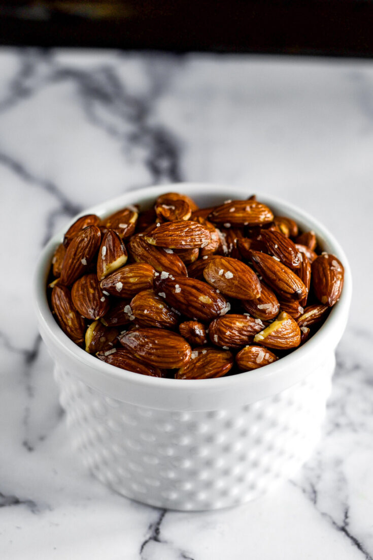 Dark brown smoked almonds dotted with coarse sugar in a white dish.