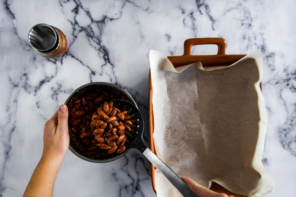 Scooping the almonds out of the bowl with a slotted spoon and placing them into a parchment lined baking dish.