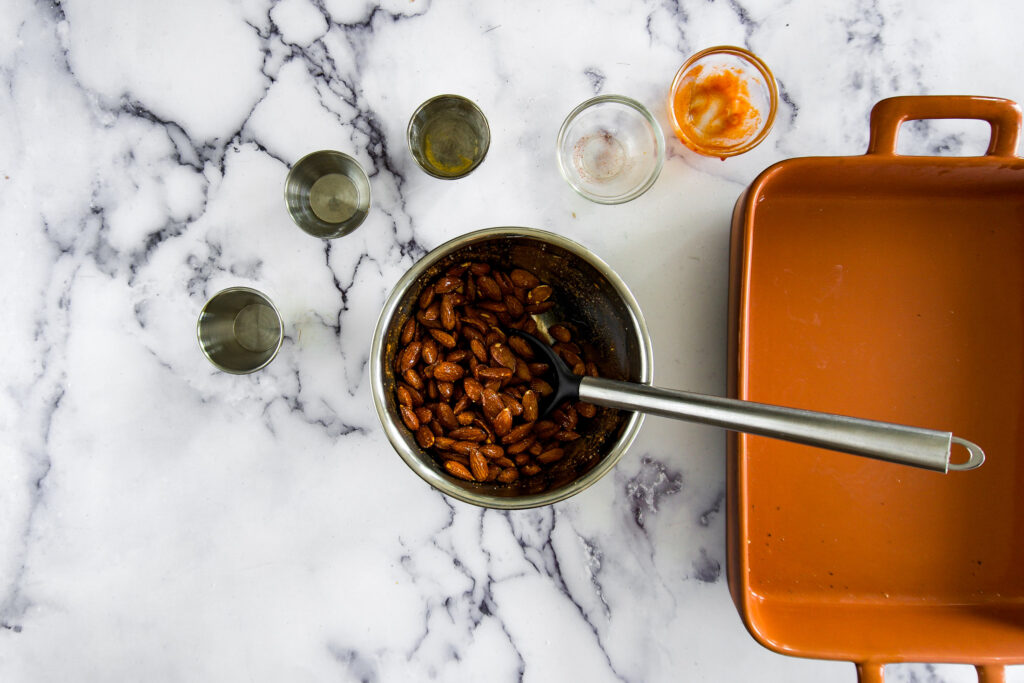 Almonds have been added to the bowl with the sweet and spicy glaze.