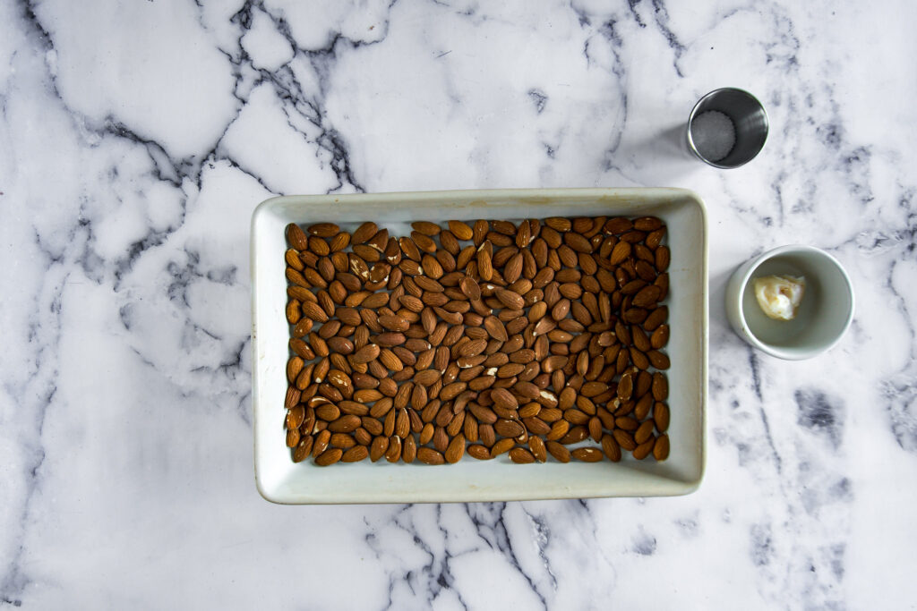 Smoked almonds in a baking dish beside bacon fat and salt.