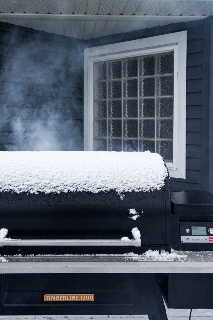Traeger Timberline 1300 covered in snow and smoking on fire up.