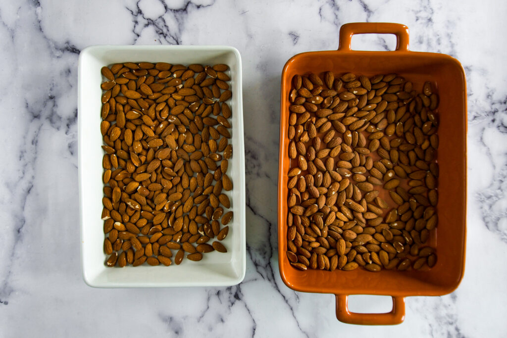 Almonds separated into 2 separate baking dishes.