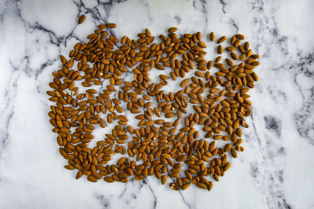 Almonds spread on a marble counter.