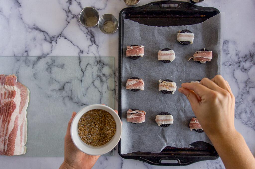 Sprinkling rub on the bacon wrapped Oreos.