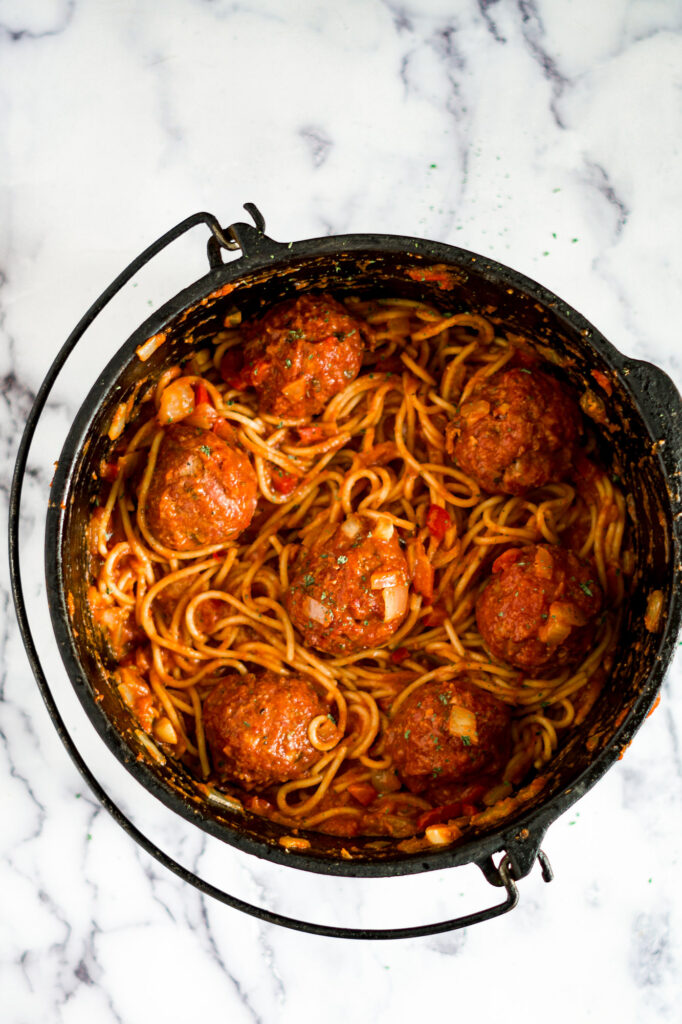 Cast iron dutch oven with spaghetti and smoked meatballs.