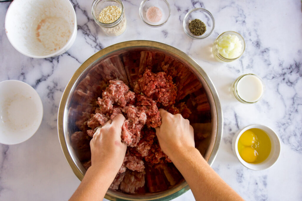 Two hands mixing the ground beef and pork.
