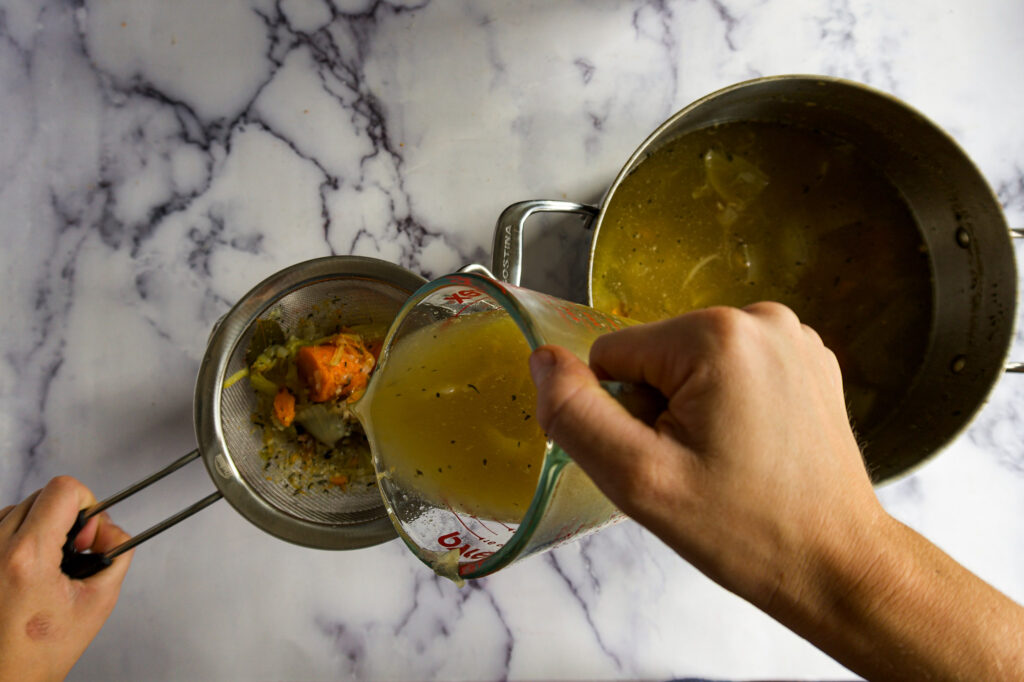 Pouring broth through the fine mesh seive.