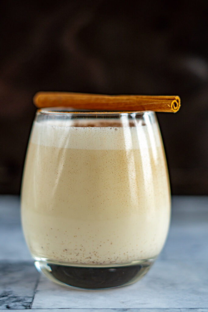 A glass of sous vide eggnog topped with a single cinnamon stick.