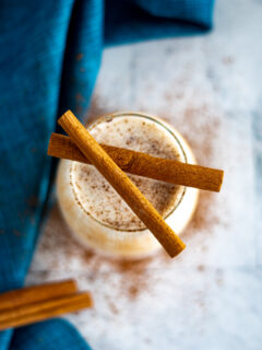 Overhead view of sous vide eggnog in a glass, garnished with ground nutmeg and two cinnamon sticks