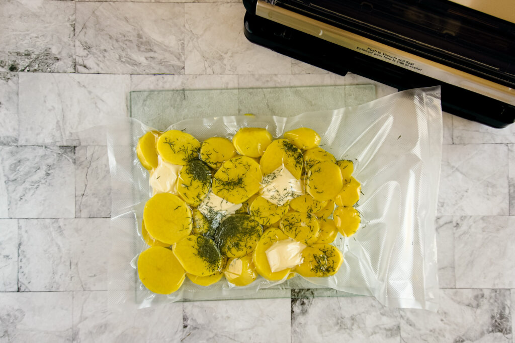 Full vacuum sealed bag with potatoes, butter and dill.