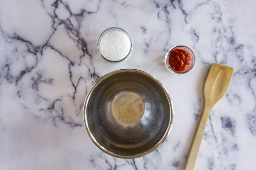 A stainless steel bowl and two jars with salt and sriracha.