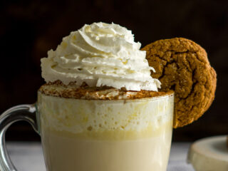 A mug of chai white hot chocolate with a gingersnap garnish.