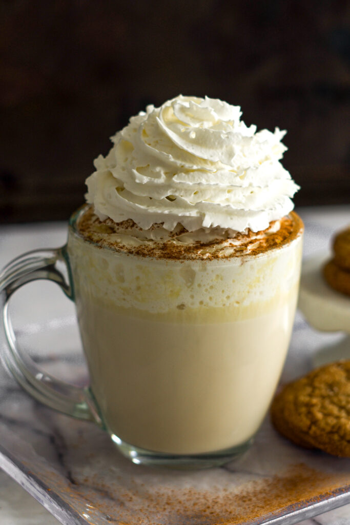 A massive pile of whipped cream on top of a clear glass mug filled with white chai chocolate.