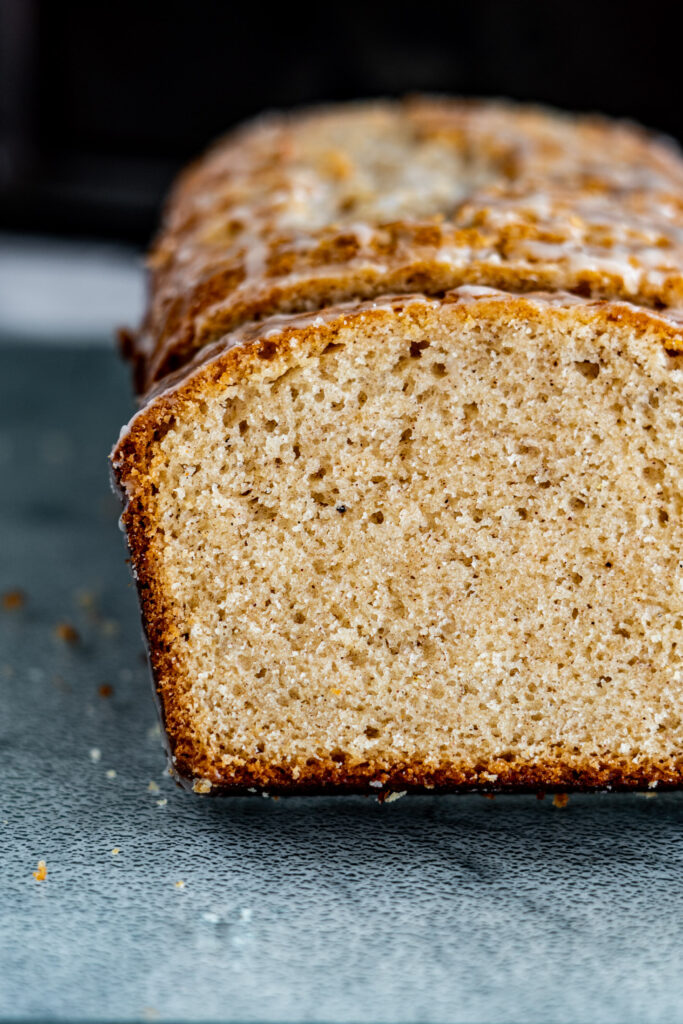 Close of sliced eggnog loaf showing the dark golden crust and pale crumb.