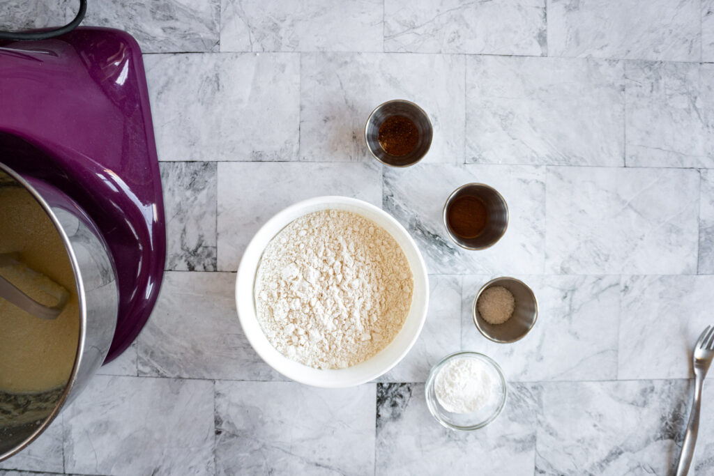 Flour in a mixing bowl surrounded by the dry ingredients.