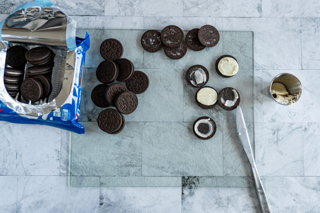 A knife scraping the creme out of the Oreo cookies.