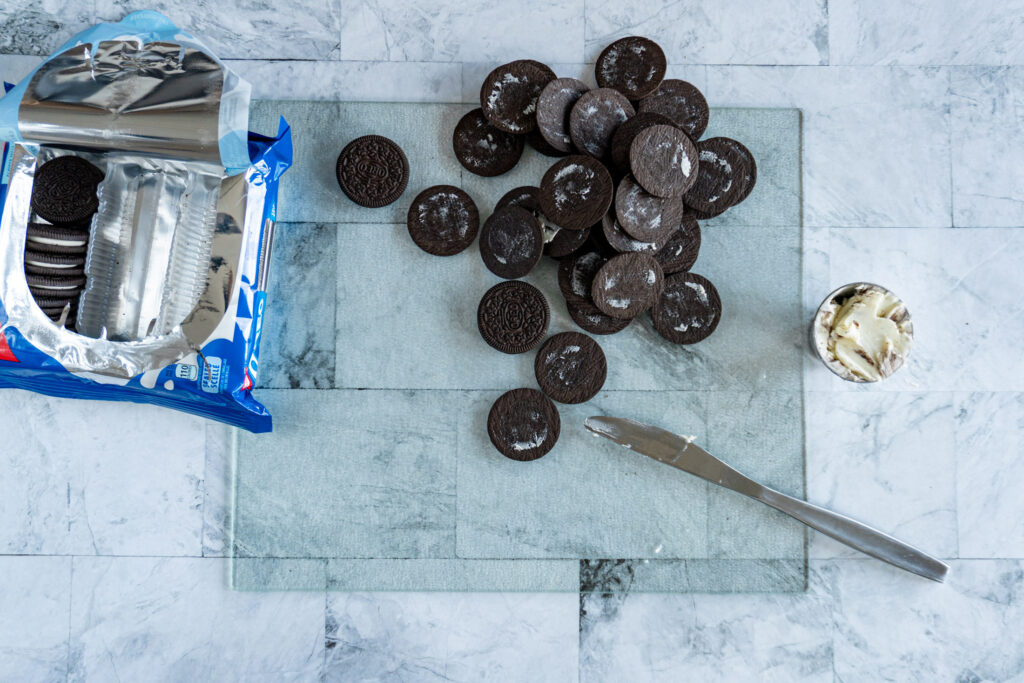Fully de-cremed Oreo cookies piled on a cutting board.