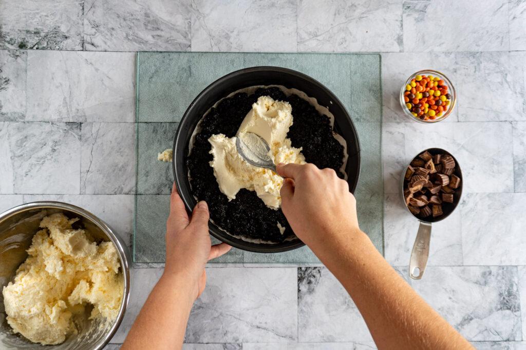 Spooning ice cream onto the cookie crus.