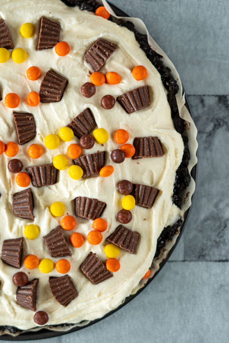 Overhead view of the ice cream pizza topped with peanut butter cups and Reece's pieces