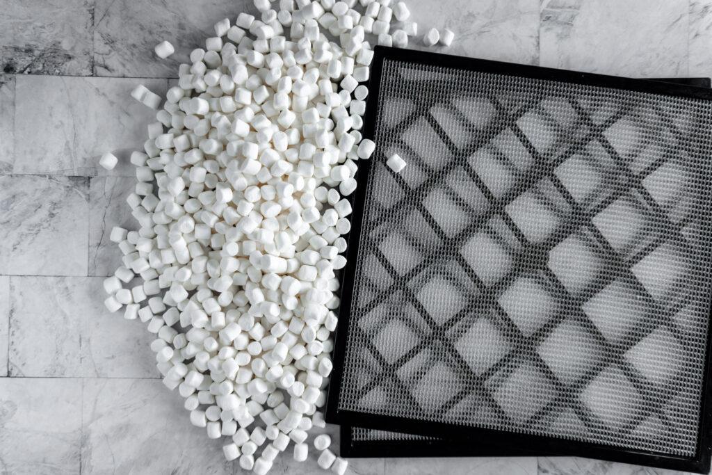 A pile of miniature marshmallows beside racks from a dehydrator.