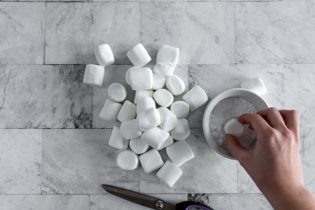 Dipping the cut end of the marshmallow in a dish of powdered sugar.