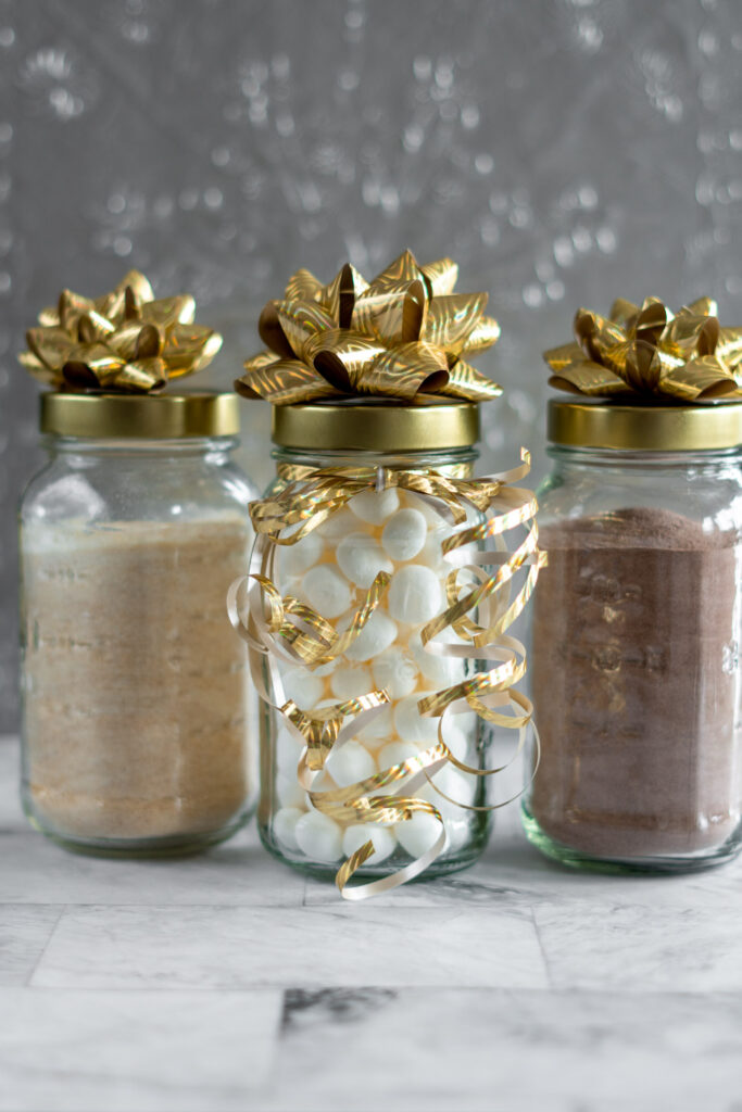 Mason jars filled with homemade hot cocoa mix and marshmallows wrapped with bows and ribbons.