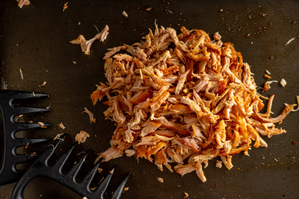 Shredded smoke chicken in a pile on a cookie sheet.