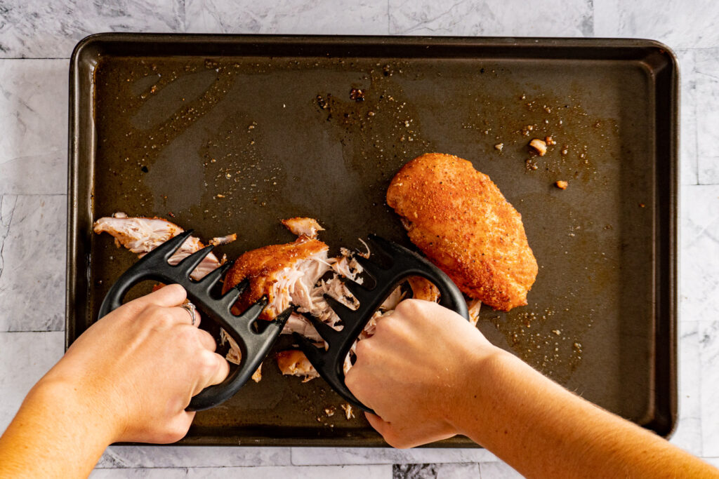 Hands using the meat claws to shred the smoked chicken breast.