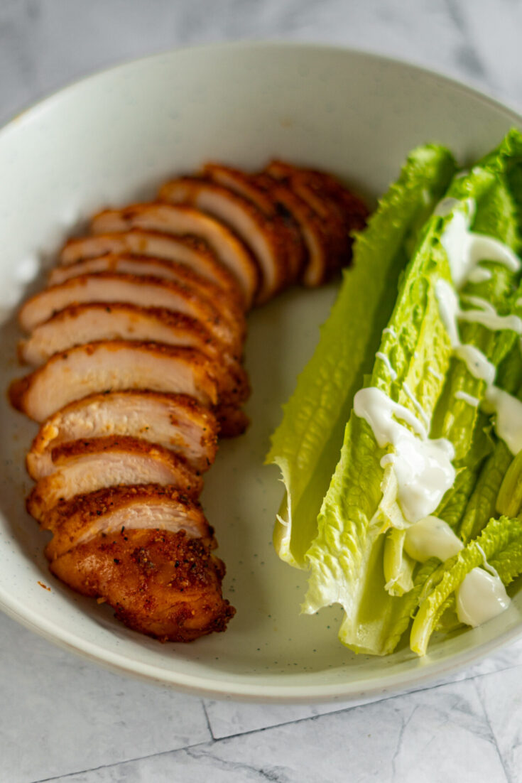 Sliced smoked chicken breast in a bowl with romaine salad.