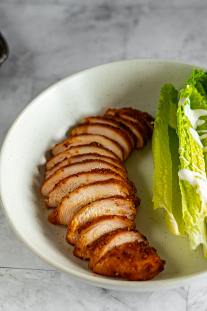 Sliced smoked chicken breast in a bowl with a chunky romaine salad