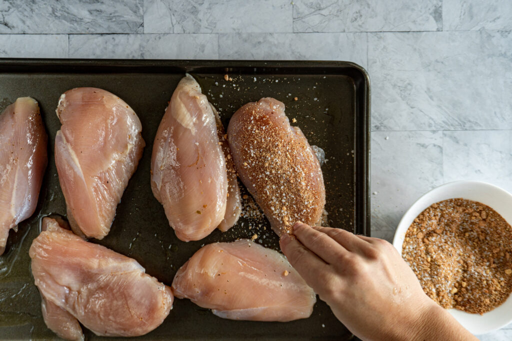 Sprinkling rub on the chicken breasts.