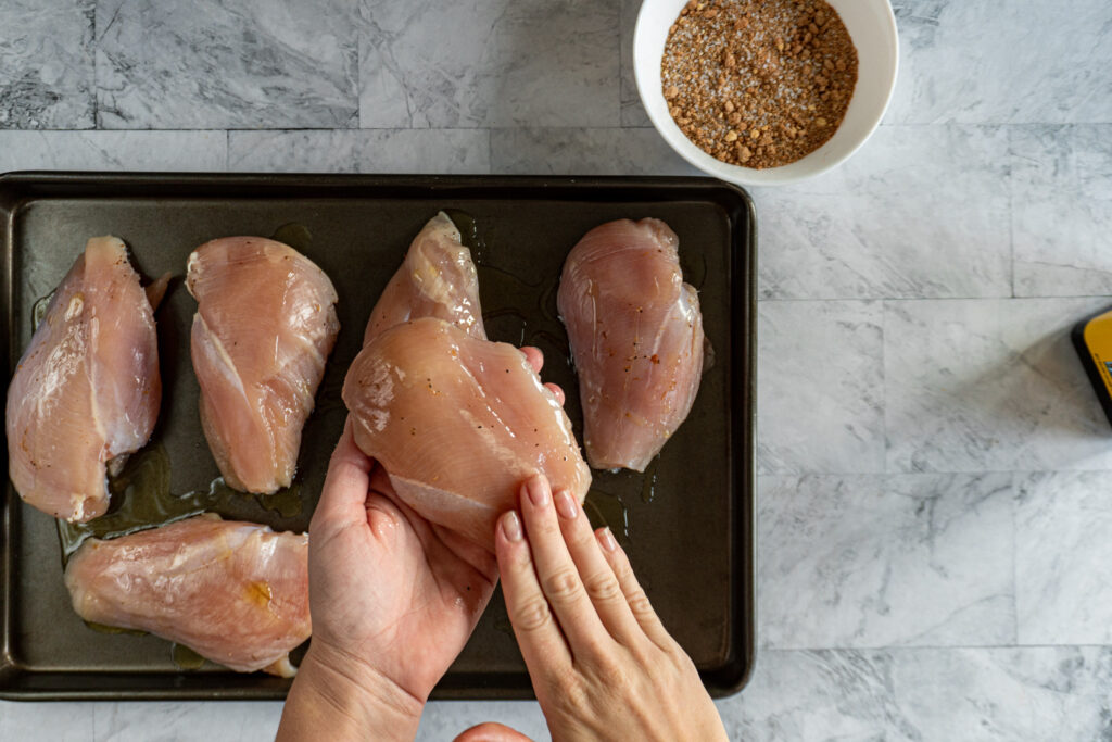 Rubbing all sides of the chicken breast with oil.