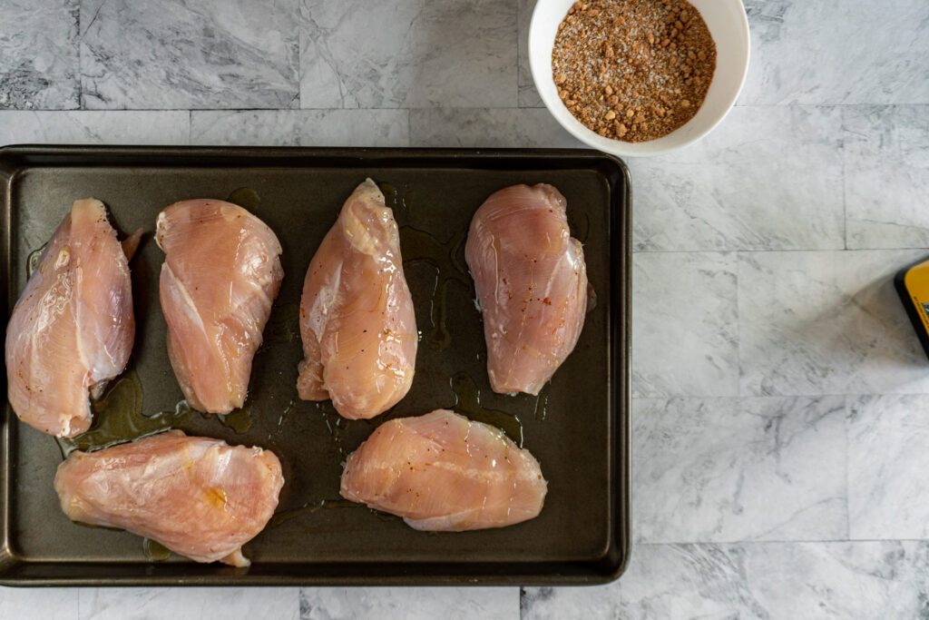 Chicken breasts drizzled with olive oil.