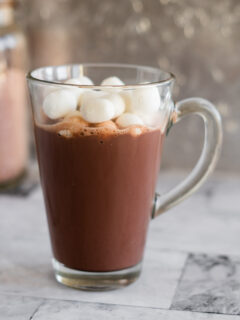 Hot chocolate in a tall mug topped with marshmallows.