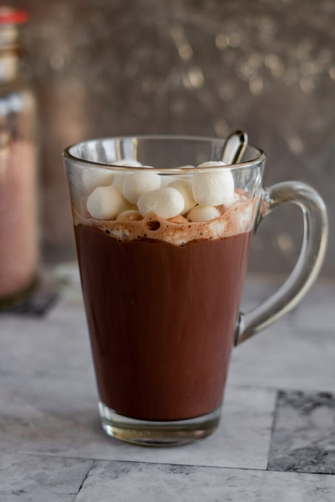 Hot chocolate in a tall glass mug with dehydrated marshmallows.