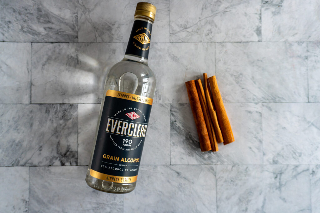 A bottle of Everclear on a table laying besides a handful of cinnamon sticks.