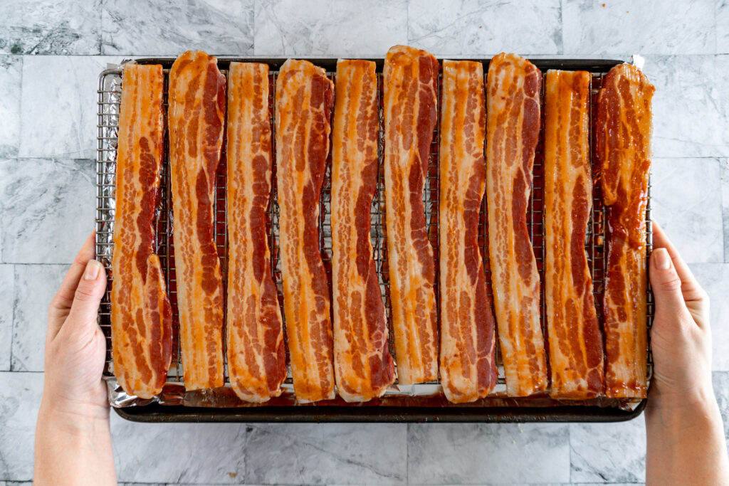 Hands carrying the tray of completely mopped bacon to the oven.