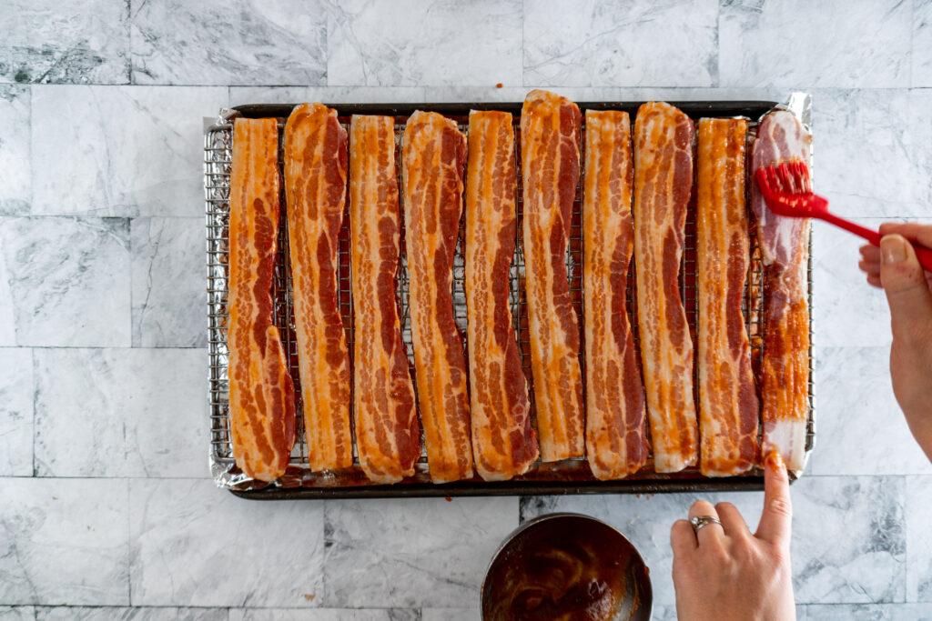 Brushing sriracha sauce on the bacon.