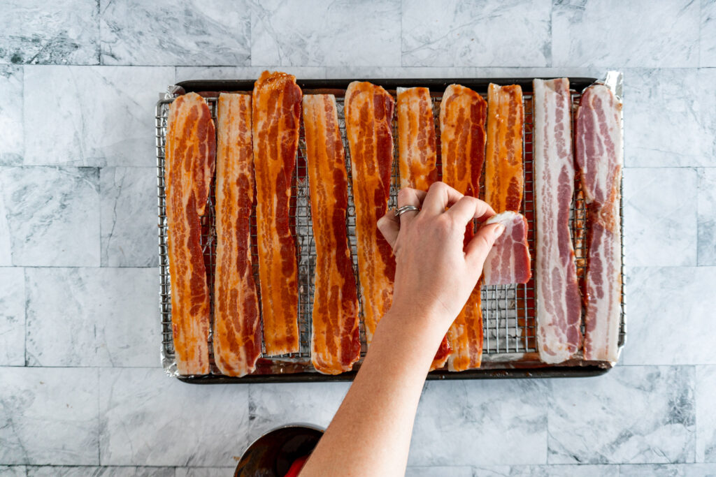 Flipping the bacon on the cooling rack.