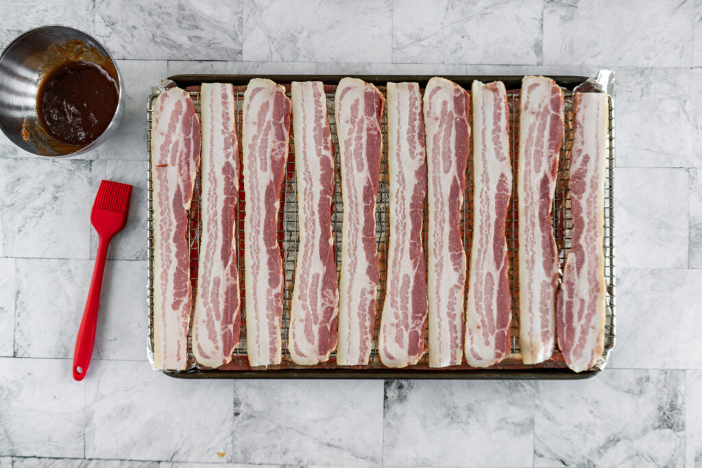 Bacon is fully laid out on the baking rack.