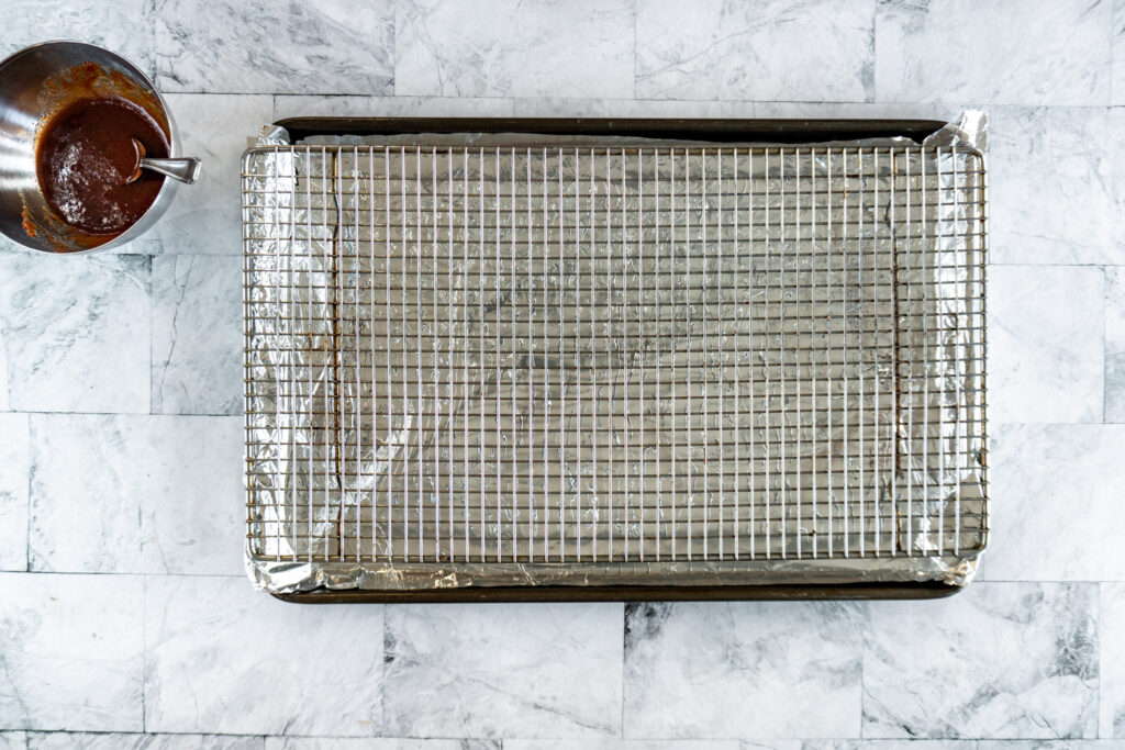 A prepared baking sheet with tinfoil and a cooling rack set on top.