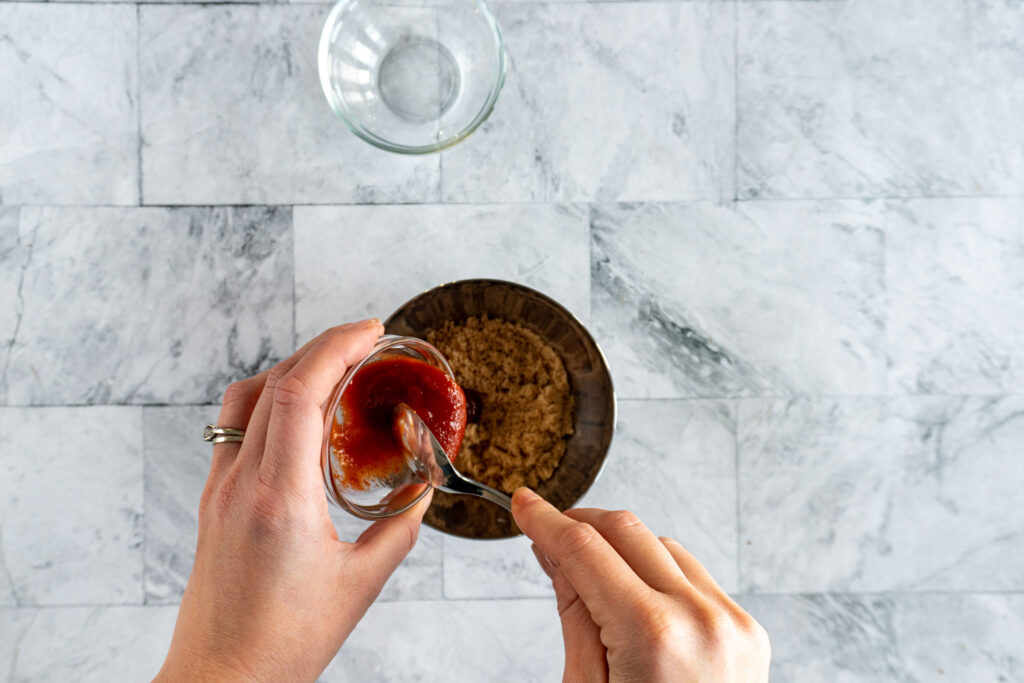 Pouring sriracha from glass bowl into bowl with brown sugar..