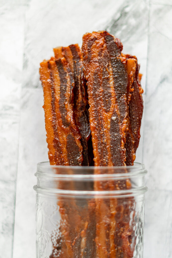 Bacon jerky stacked in a wide mouth mason jar.
