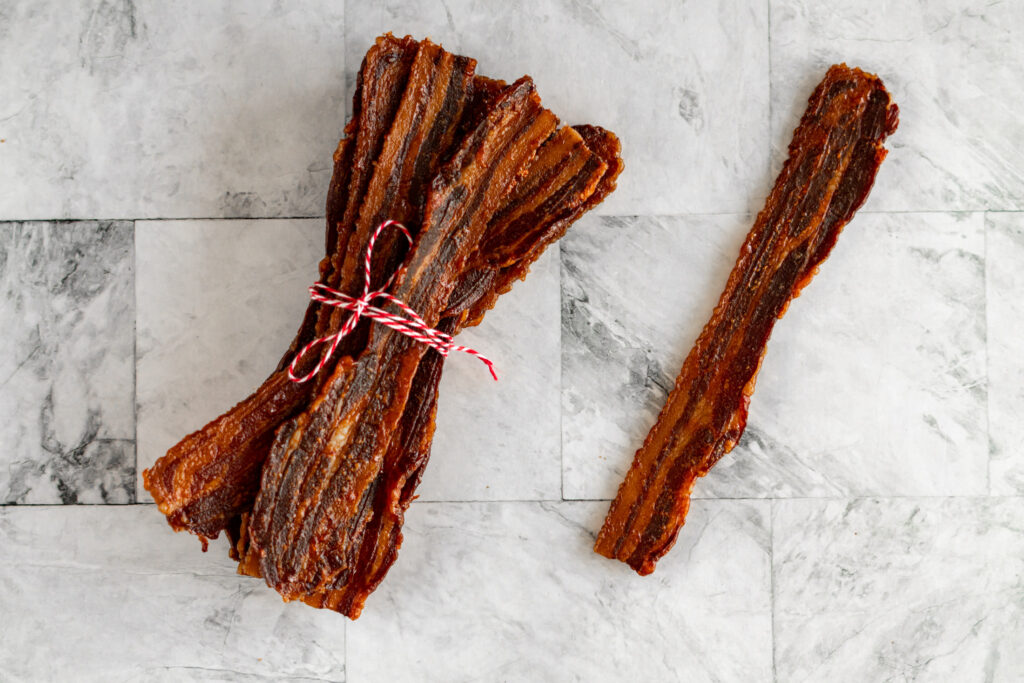 Bacon jerky wrapped in red and white twine with one piece out.