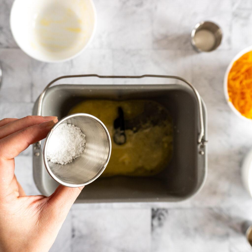 Pouring kosher salt into bread machine pan.