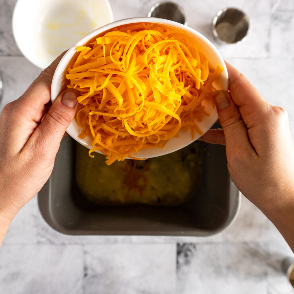 Adding shredded cheese to the wet ingredients in the baking pan.