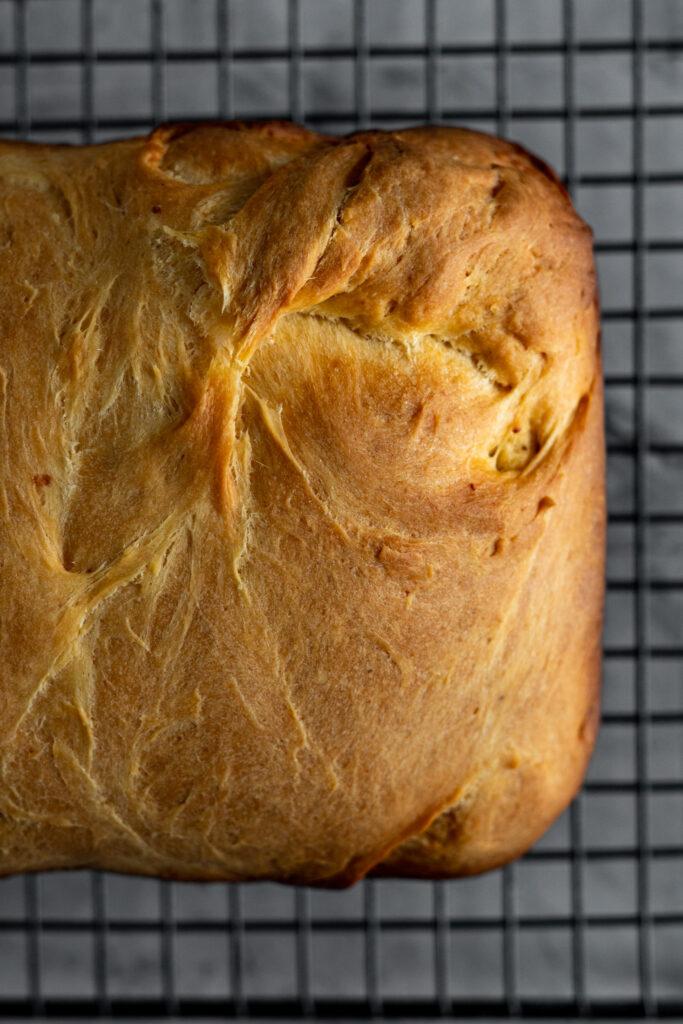 Close up of the orange crust of this bread machine recipe.
