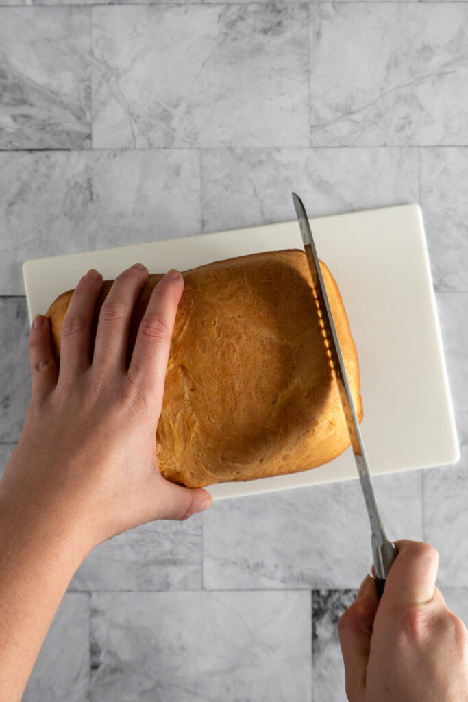 Cutting the end off an orange loaf of bread machine cheese bread.