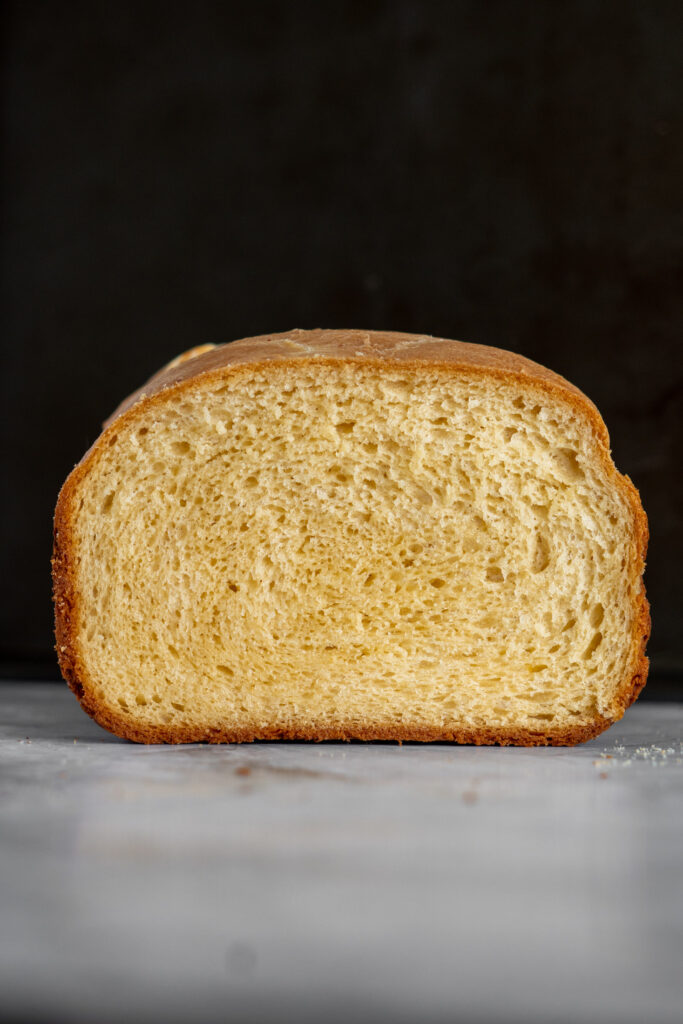 Cross section of cheese bread against a black background.