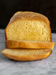 Sliced bread machine cheese bread showing the dark crust and orange tinged crumb.